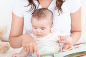 Attentive mother showing images in a book to her cute little son — Stock Photo