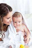 Madre encantada secado a su bebé después de su baño — Foto de Stock