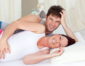 Laughing caucasian pregnant woman lying on bed with her husband — Stock Photo