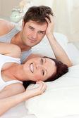Radiant caucasian couple lying on bed — Stock Photo