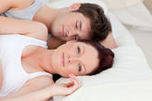 Bright caucasian couple lying on bed — Stock Photo