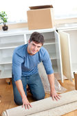 Cute man rolling a carpet out — Stock Photo