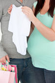 Close-up of a pregnant woman holding baby cloth — Stock Photo