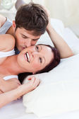 Cheerful caucasian couple lying on bed — Stock Photo