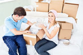 Concentrated young couple unpacking boxes with glasses — Stock Photo