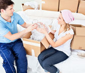 Affectionate young couple unpacking boxes with glasses — Stock Photo