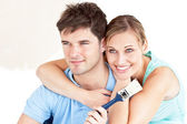 Smiling caucasian couple painting a room — Stock Photo