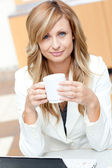 Bright businesswoman holding a cup of coffee in front of her lap — Stok fotoğraf
