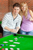 Caucasian couple playing cards on a billiard — Stock Photo