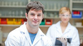 Two concentrated scientists looking at the camera standing — Stock Photo