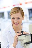 Erfreut weibliche wissenschaftler mit einem mikroskop — Stockfoto
