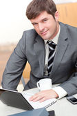 Busy businessman with a laptop, a cellphone and a mug sitting at — Stock Photo