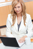 Attractive businesswoman using her laptop with a mug and food in — Stock Photo