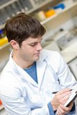 Concentrated scientist writing on a clipboard — Stock Photo