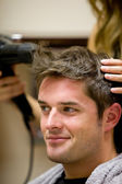 Female hairdresser drying her male customer's hair — ストック写真