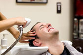 Handsome man having his hair washed — Stock Photo