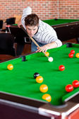 Concentrated young man playing snooker — Стоковое фото