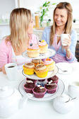 Two cute friends eating cupcakes sitting in the kitchen at home — Stock Photo