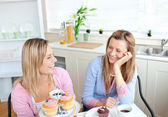 Laughing women eating cupcakes and drinking coffee sitting in th — Stock Photo