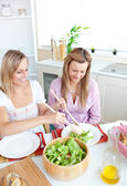 Two healthy women eating salad in the kitchen during lunchtime a — Stock Photo