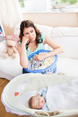 Bored mother waiting for her baby to wake-up sitting in the sofa — Stock Photo