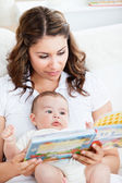 Attentive mother reading a book to her adorable baby sitting in — Stock Photo