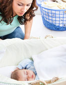 Attentive mother keeping an eye on her baby sleeping in his crad — Stock Photo
