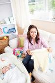 Alegre joven madre sosteniendo un pijama de bebé sentado en el sofá en h — Foto de Stock