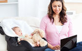 Bright mother working on a laptop with her baby sitting next to — Stock Photo