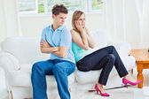 Angry couple sitting on the sofa back to back after a quarrel — Stock Photo