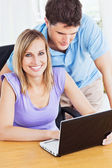 Portrait of a cheerful woman and her attentive boyfriend using a — Stock Photo