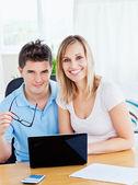 Retrato de una pareja alegre usando una laptop sentados juntos en — Foto de Stock