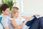 Cute couple browsing a book lying on the sofa — Stock Photo