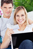 Glad couple buying online with credit card and laptop laying on — Stock Photo