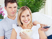 Portrait of an attractive couple with pop-corn and remote relaxi — Stock Photo