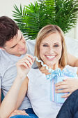 Happy woman unwrapping a present lying on the sofa with her boyf — Stock Photo