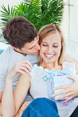 Attentive man kissing her girlfriend after giving her a present — Stock Photo