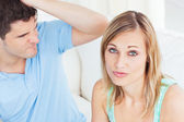 Young woman ignoring her boyfriend sitting on the sofa at home — Stock Photo