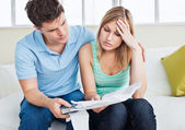 Worried woman looking at bills with her boyfriend holding a calc — Stock Photo