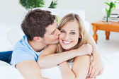Portrait of an attentive boyfriend kissing his smiling girlfrien — Stock Photo