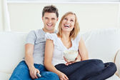 Joyful couple watching a movie with pop-corn sitting on the sofa — Stock Photo