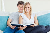 Cute couple reading a book together sitting on the couch at home — Stock Photo