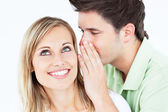 Young man whispering something to his attentive female friend — Stock Photo