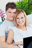 Portrait of a young caucasian couple with laptop relaxing on the — Stock Photo