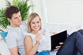 Happy couple with credit card and laptop resting on the sofa dur — Stock Photo