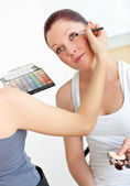 Close-up of a woman making-up her female friend at home — Foto Stock
