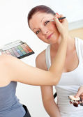 Happy young woman with make-up accessories being made-up by a fr — Foto Stock