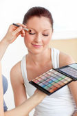 Attractive woman having a make-up lesson at home — Stok fotoğraf