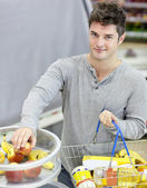 Healthy man with shopping-basket buying fruits in a grocery shop — Stock Photo
