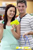 Portrait of a young couple buying cans standing in a grocery sho — Stock Photo